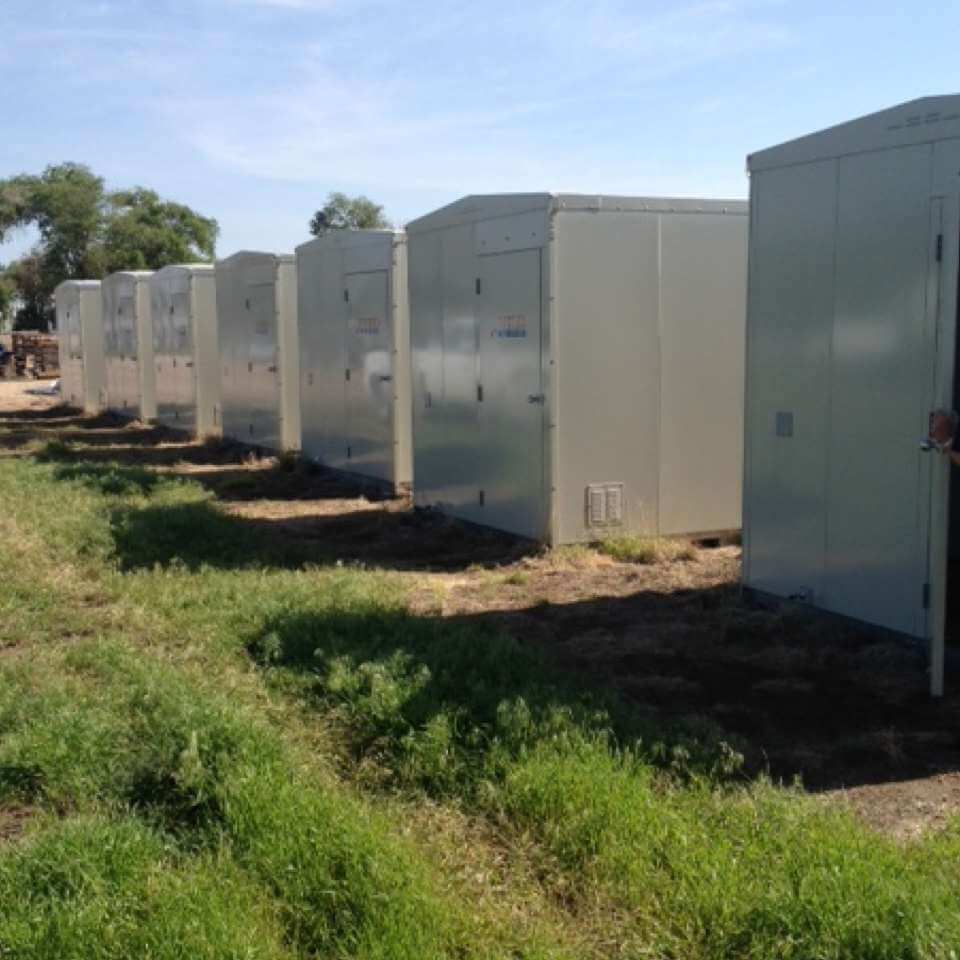 Row of 8x12 communication shelters in a staging yard for United Wireless